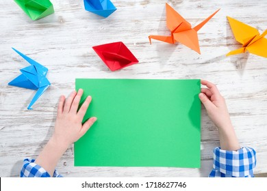 The child makes origami from colored paper.