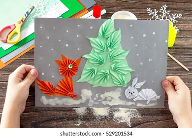The child makes a paper Christmas tree, snow, fox and bunny. Children's art project, a craft for children. Copy space.