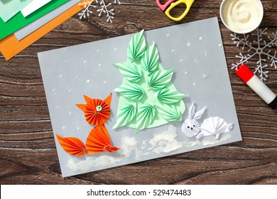 The child makes a paper Christmas tree, snow, fox and bunny. Children's art project, a craft for children. Copy space. Craft for kids.