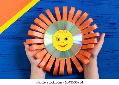 Child makes smiling sun from CD. Children's art project. DIY concept. Step-by-step photo instruction.