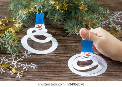 The child makes a toy on the Christmas tree snowman paper. Glue, paper, scissors on a wooden table. Children's Art Project, hobbies, hand made, craft for children.
