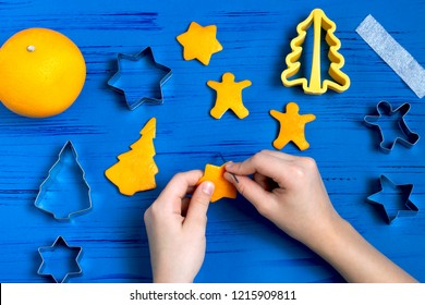 Child making decorations of orange peel for Christmas. Children's art project. DIY concept. Step by step photo instruction. Step 4. Make hole in figures for cord