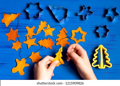 Child making decorations of orange peel for Christmas. Children's art project. DIY concept. Step by step photo instruction. Step 6. Collect figures on string