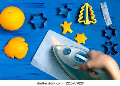 Child making decorations of orange peel for Christmas. Children's art project. DIY concept. Step by step photo instruction. Step 3. Straighten and slightly dry figures with iron