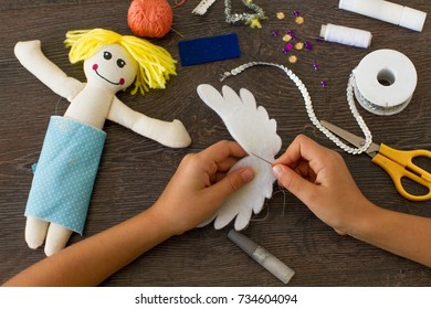 Child making a felt angel doll with sewing supplies on  wooden table.