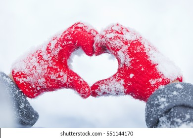 child making heart symbol with snowy hands, saint valentines day, girl hands in red mittens, boy, woman, baby, human hands in red gloves folded in the shape of hear on snow