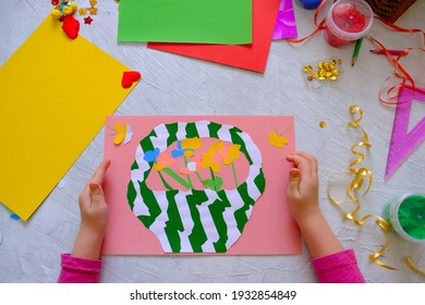 Child making homemade greeting card. little girl making  basket with flowers from paper and clay, plasticine as gift for Mothers day or Valentines day . Traditional play concept. Arts  crafts concept.
