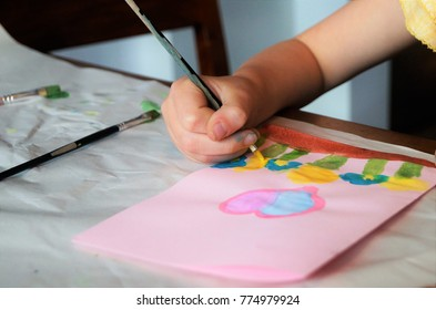Child making homemade greeting card. A little girl paints a heart and flowers on a homemade greeting card as a gift for Mother's Day. Traditional play concept. Arts and crafts concept.