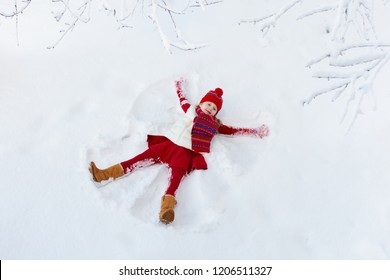 Child making snow angel on sunny winter morning. Kids winter outdoor fun. Family Christmas vacation. Little girl playing in snow after heavy storm. Active children outdoors on Xmas day.