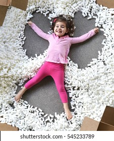 Child making snow angel with packing foam