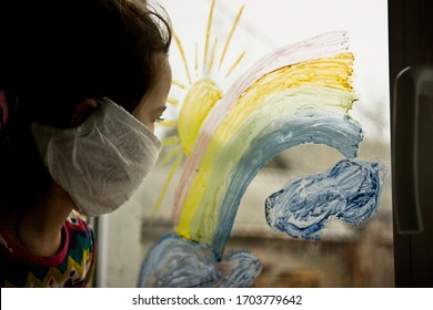 A child in a medical mask looks through the glass to the street. The kid draws a rainbow on a window pane as a symbol of a dream and hope for the future. The kid is sad on the street sitting at home i