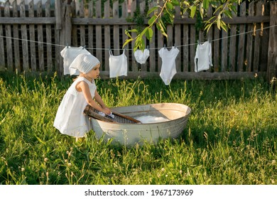 The child merrily washes his clothes in the basin. Splashes of water and foam from washing clothes. A girl in a white dress hangs out wet underwear to dry. Washing in an old basin.