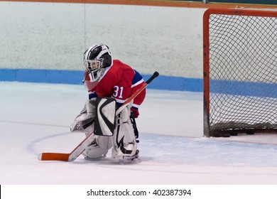 Child minor ice hockey goaltender in net ready for the puck during a game