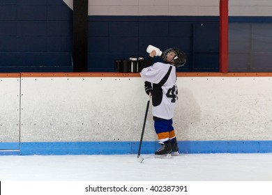 Child minor ice hockey player drinking water by the arena boards during rest period in practice