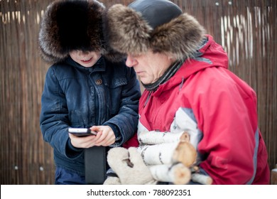 Child with mobile phone in hands showing to grandfather how to use it. Different generations. Family time.