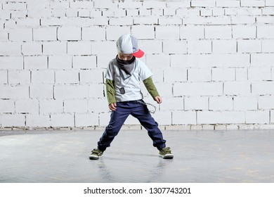 Child model posing in young rapper clothes. Cool kid boy dancing break dance.Hip-hop style. studio, brick wall background.