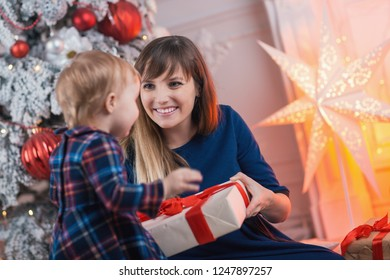 Child with mom with gifts near the Christmas tree. Mother and little daughter together with present indoors. New Year's and Xmas holidays.