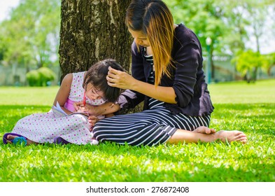 child and mom relax in the park