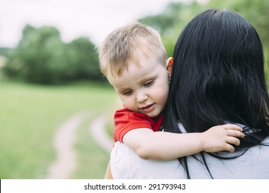 child and mom walk in the summer park. sad crying baby