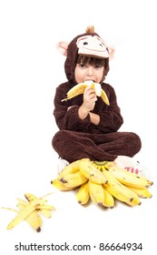 Child with monkey costume eating banana