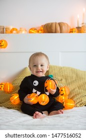 A child in a monster costume sits on a bed among garlands with pumpkins. All Saints Day Celebration