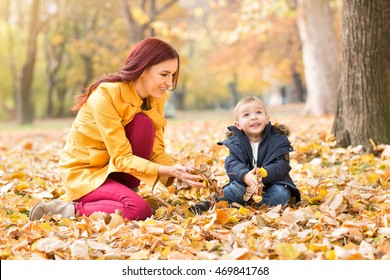 Child and mother in the autumn park playing with leaves