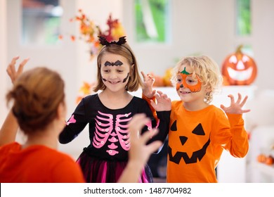 Child and mother in Halloween costume. Kids trick or treat. Face painting for party event. Little boy dressed as evil vampire and girl in witch hat with pumpkin lantern. Family celebration.