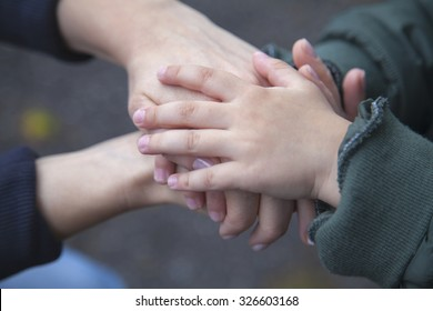 Child and mother holding hands in unity and supporting each other.