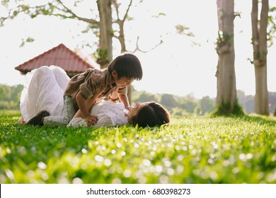 child with mother playing at park,happy family concept.