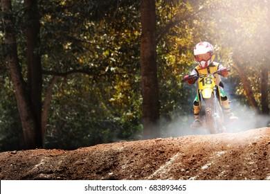 Child Motocross bike jump on track.