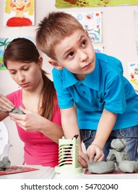 Child  mould from clay with teacher. Child care.
