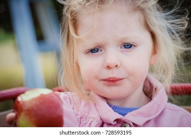 Child with mouthful offering a bite of her apple