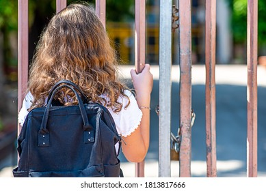 Child near the gate of the closed school. Back view blonde teenage girl outside a closed school fence.