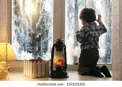 A child in the new year looks out the window. Children are waiting for Santa Claus. A child in Santa suit sits at the window.
