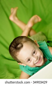 child with notebook on bed