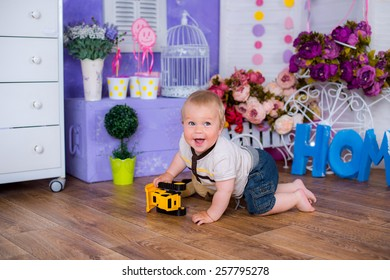 child in the nursery playing with toy car on his birthday very happy
