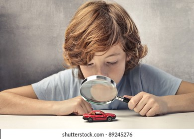 Child observing a toy-car through a magnifying glass