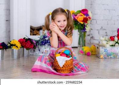 child on the background in the colors of the room in a bright room in a color dress holding an Easter egg yellow and listen what's inside.