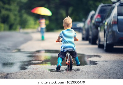 child on a balance bicycle at asphalt road in summer. Bike in the park moving through puddle on rainy day