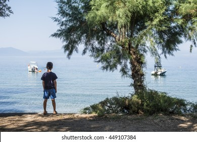 Child on the beach looking at the sea and boats.