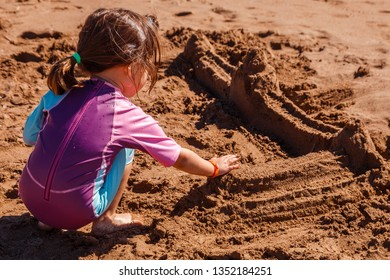 A child on the beach plays with sand. Girl building a sand castle.