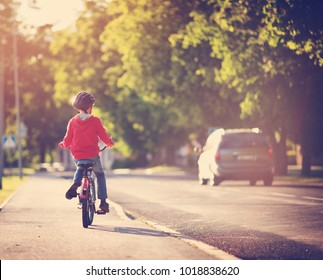 child on a bicycle at asphalt road in summer. Bike in the park. Boy cycling outdoors on beautiful sunny evening