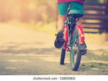 child on a bicycle at asphalt road in early morning