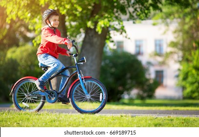 child on a bicycle at asphalt road in summer. Bike in the park