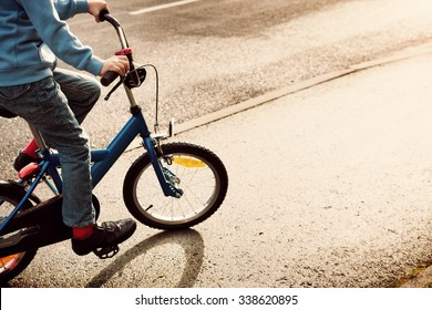 a child on a bicycle in part on asphalt road