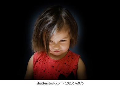 child on dark bakground look up and smiling sly. little girl devious