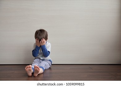 The child on the floor cries and closes his face with his own hands. Hiding.