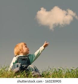 child on green grass under blue sky