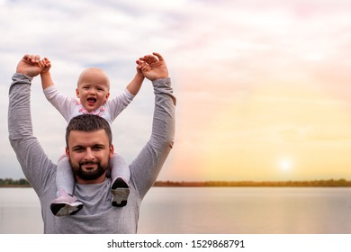 A child on his father's neck. Walk near the water. Baby and dad against the sky