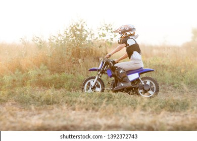 Child on his small motorcycle. Small biker dressed in a protective suit and helmet. The kid is engaged in motocross.